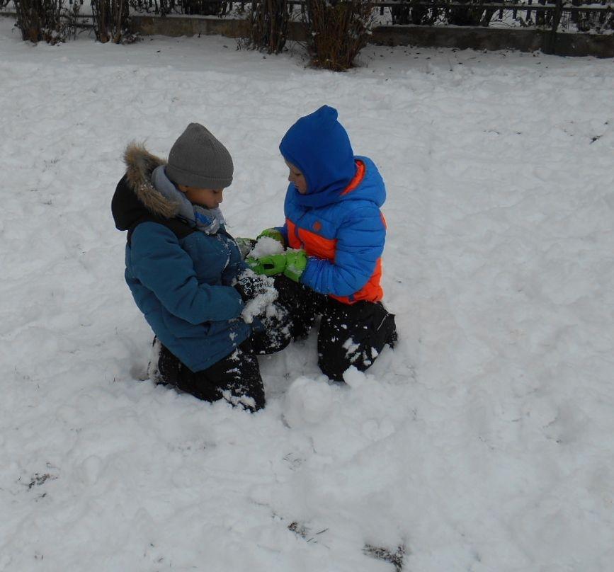 Chlapci spolupracují na sněhu.