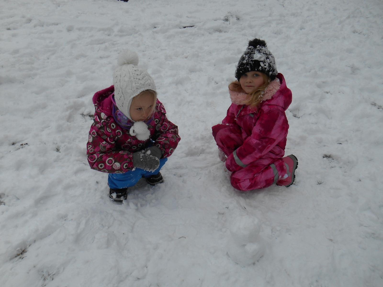 Děvčata tvoří sněhuláčka.