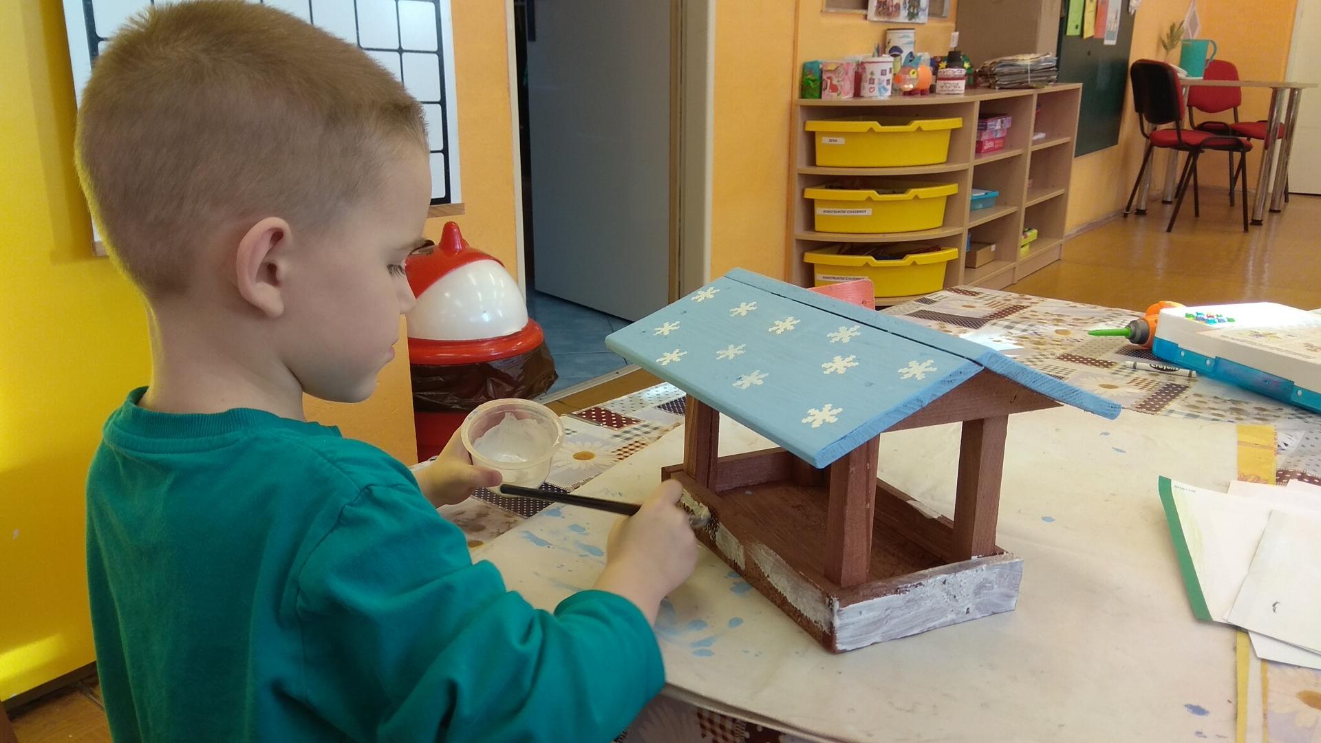 Chlapec zdobí krmítko.
