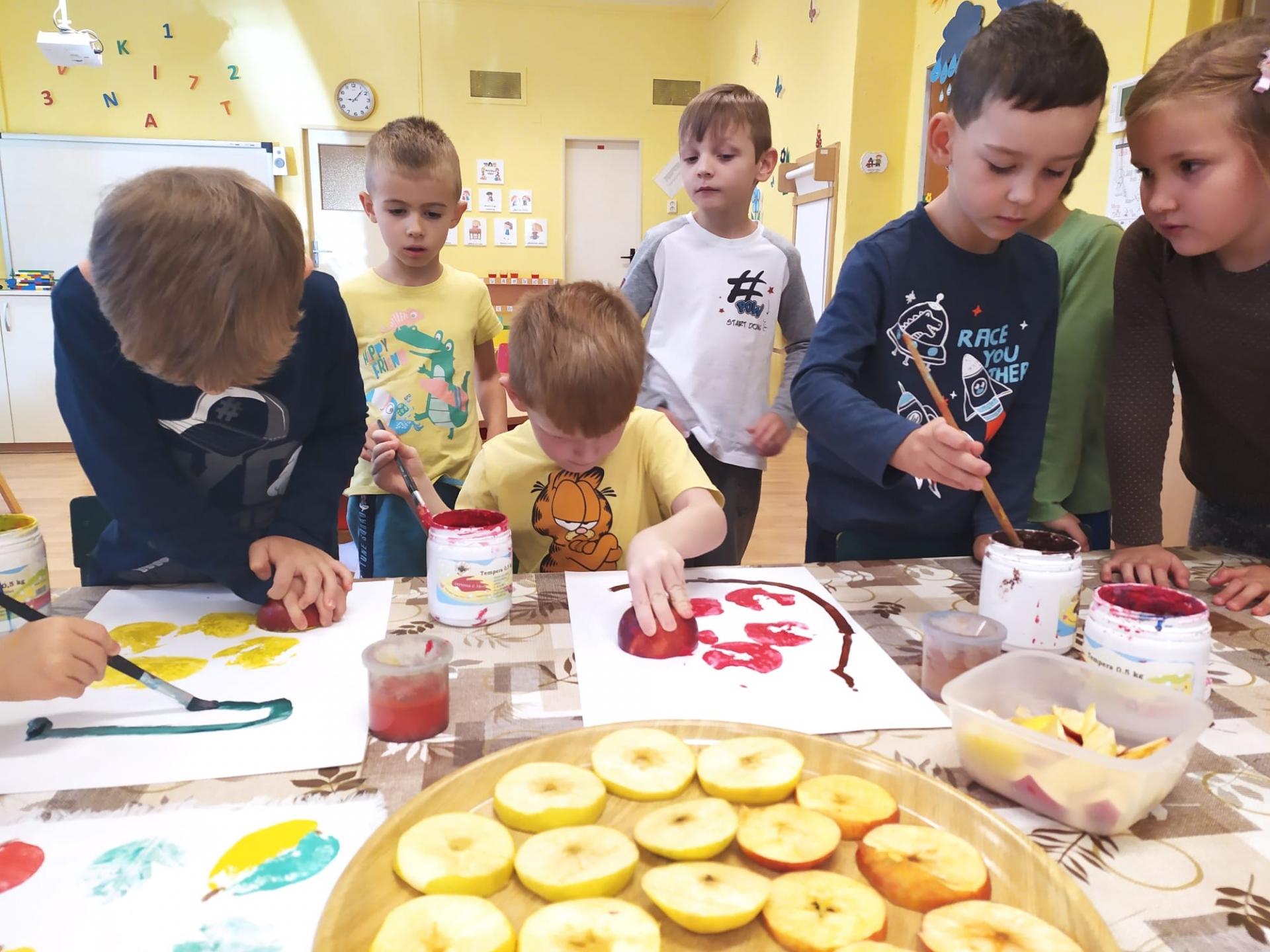 Děti tvoří z jablek.