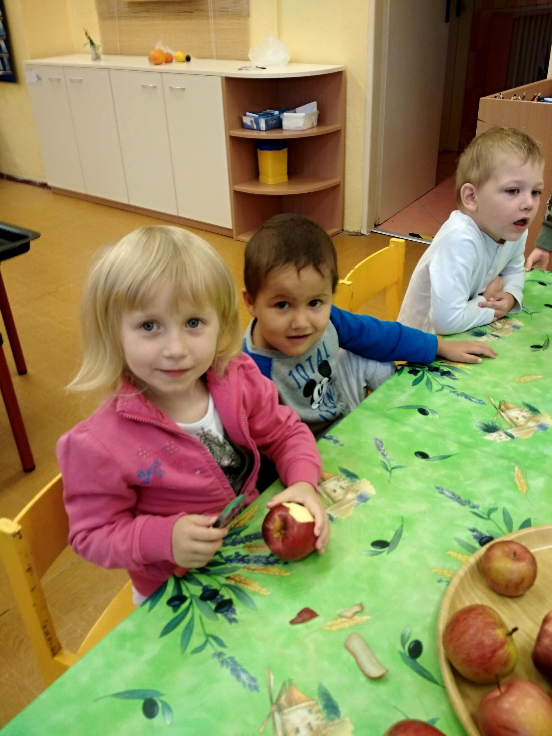 Děti škrábou jablíčka.