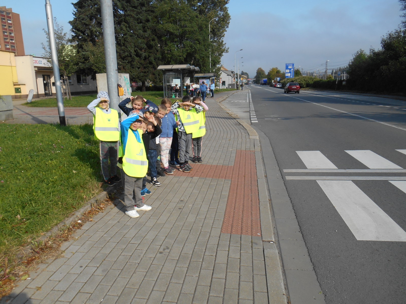 Předškoláci pozorují provoz u silnice.